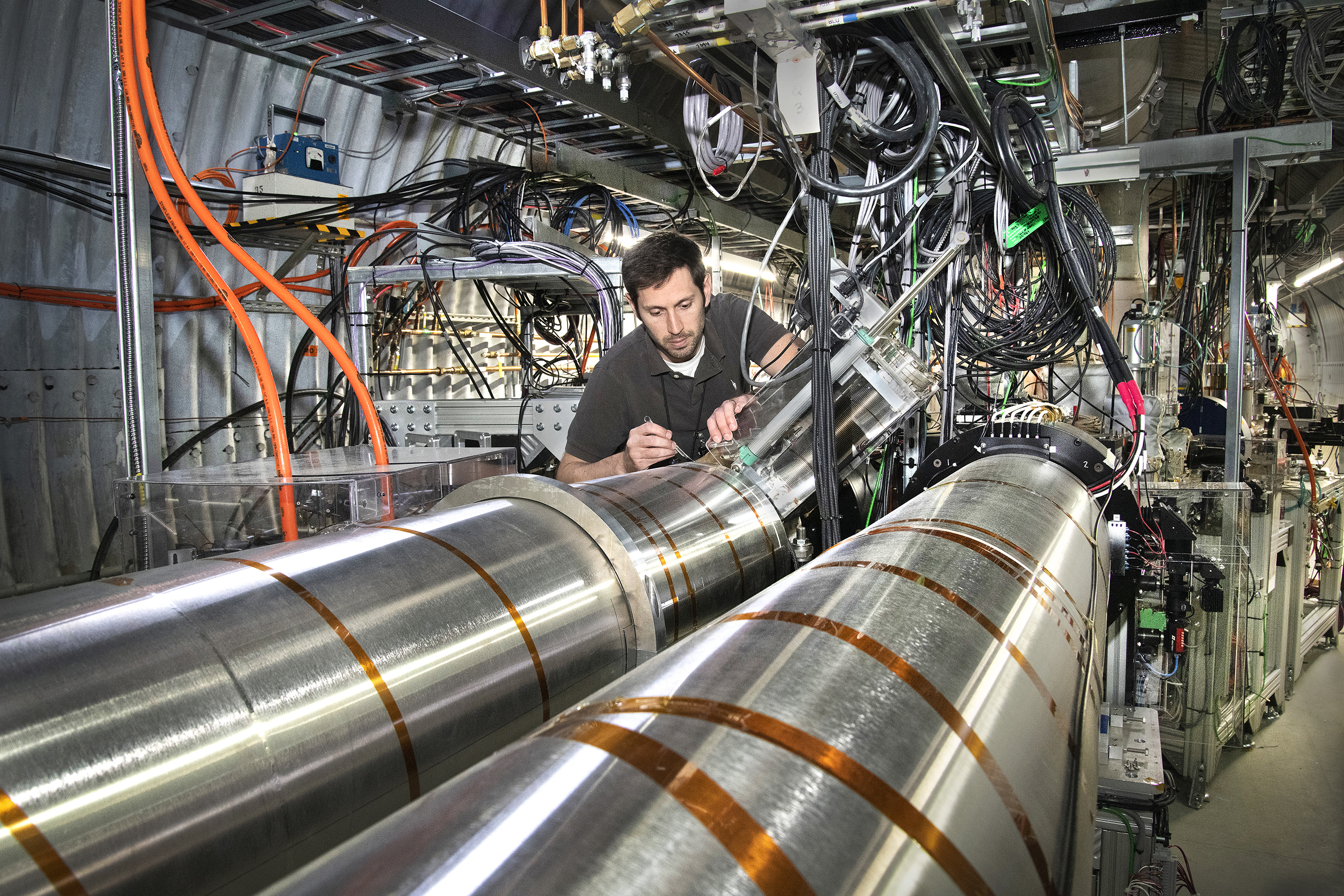 Brookhaven Lab engineer Mathew Paniccia next to the LEReC cooling sections. Electrons have successfully cooled bunches of ions in these cooling sections of the Relativistic Heavy Ion Collider (RHIC).