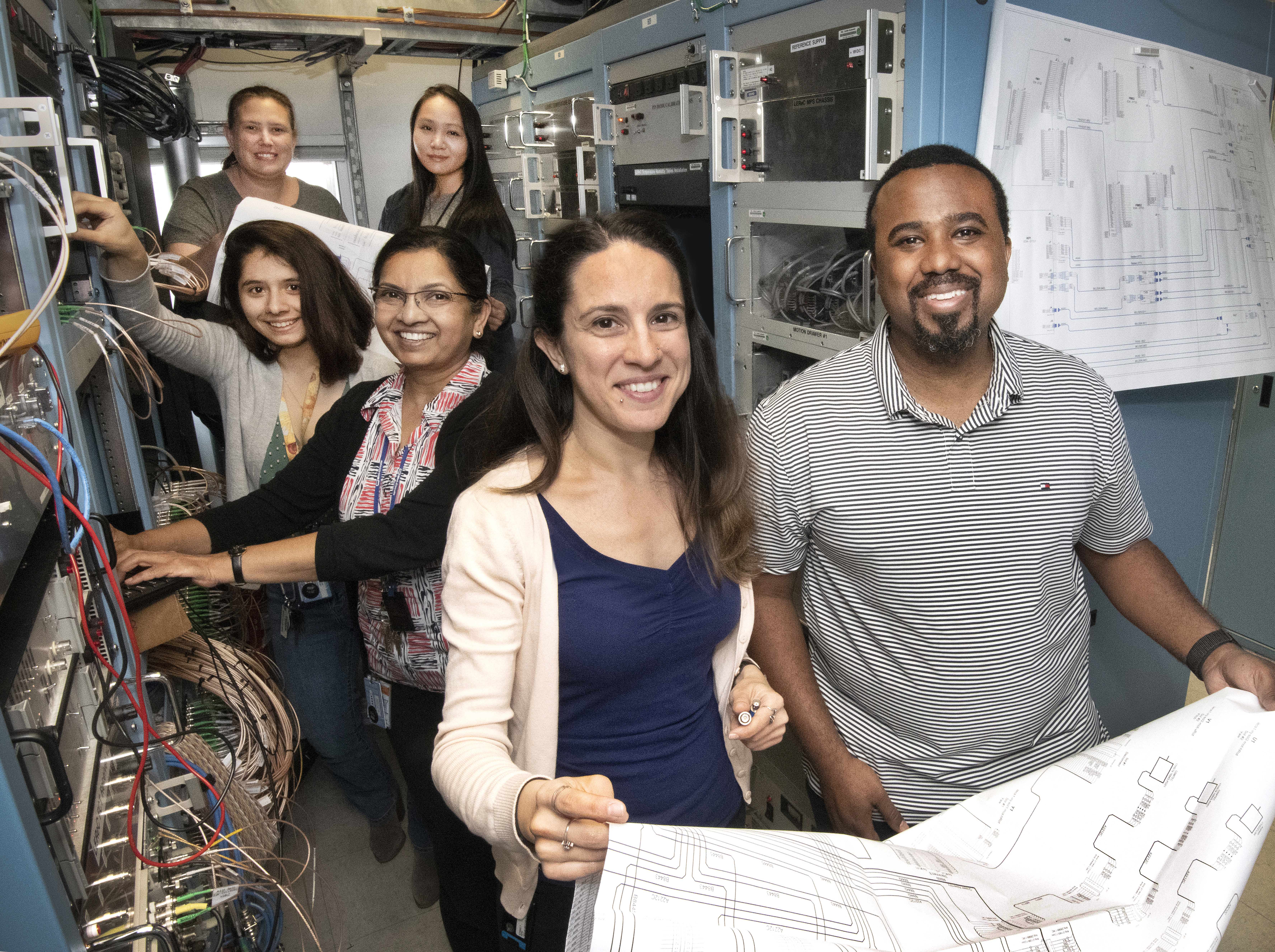 Collider-Accelerator Department engineers and technicians with high-tech custom electronics equipment required for successful beam operations (from rear, l to r): Loralie Smart, Linh Nguyen, Kayla Hernandez, Geetha Narayan, Zeynep Altinbas, Theodoro Samms.