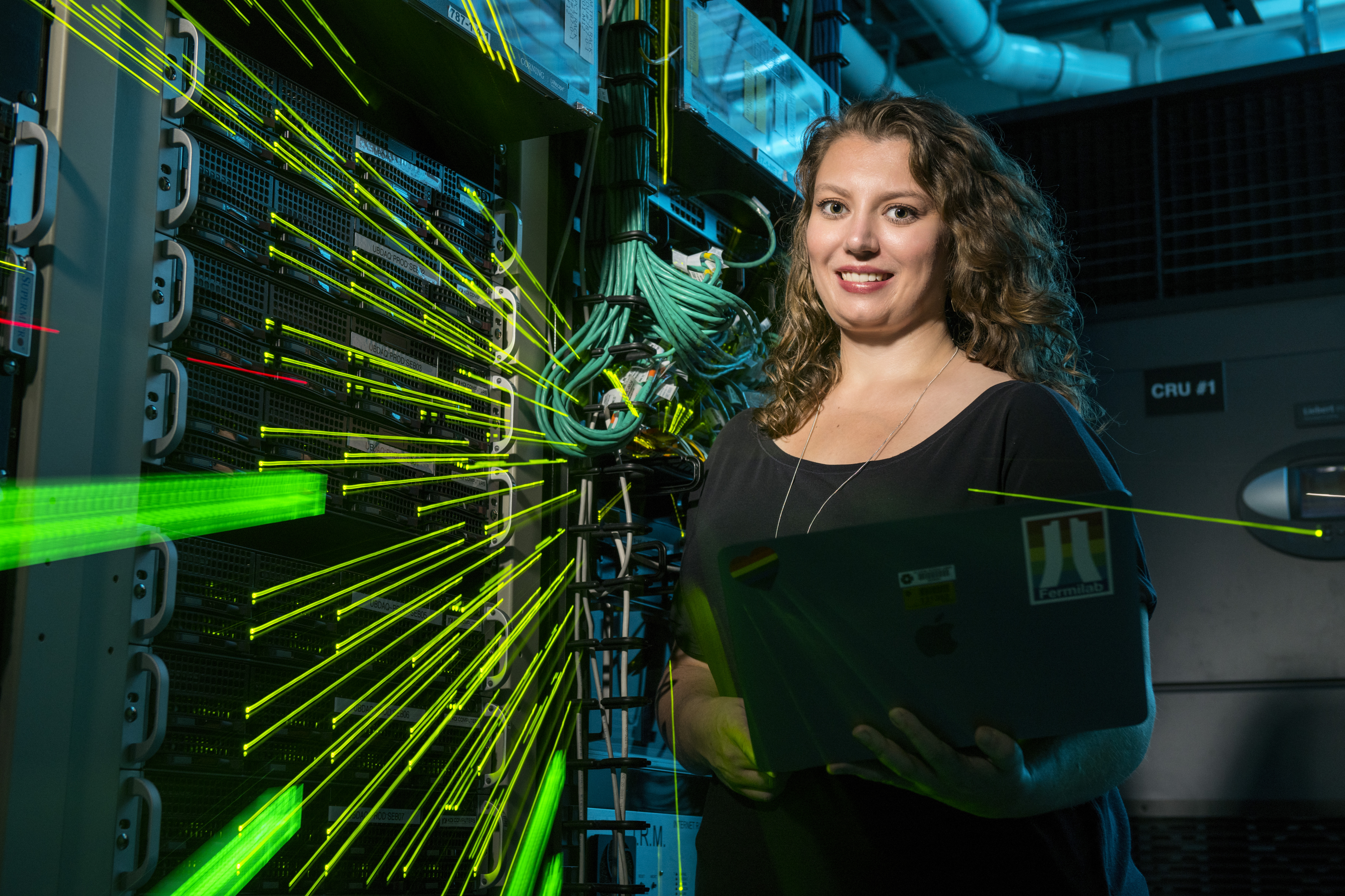 Kirsty Duffy with electronic racks used for the MicroBooNE detector.