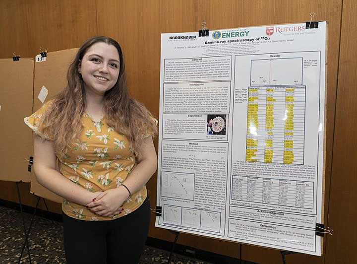Stecenko with a poster from a previous project at Brookhaven Lab on gamma ray spectroscopy, Fall 2019